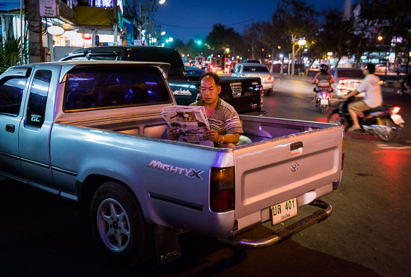 Man reading newspaper in the back of a pickup truck in Chiang Mai, Thailand. Photo by Jim Newberry.
