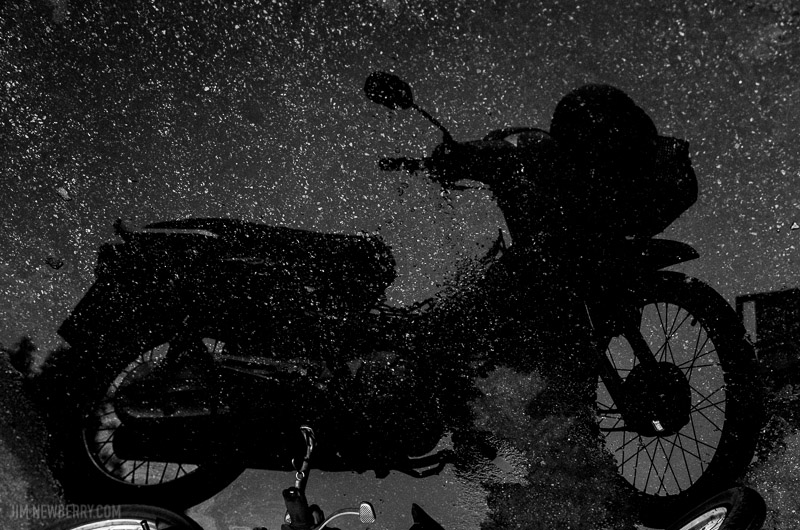 Motorbike reflected in puddle, looks like it's in the sky with stars. Photo by Jim Newberry.