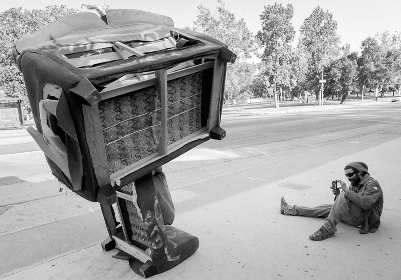 Man taking a picture of furniture sculpture on Figueroa in Los Angeles.