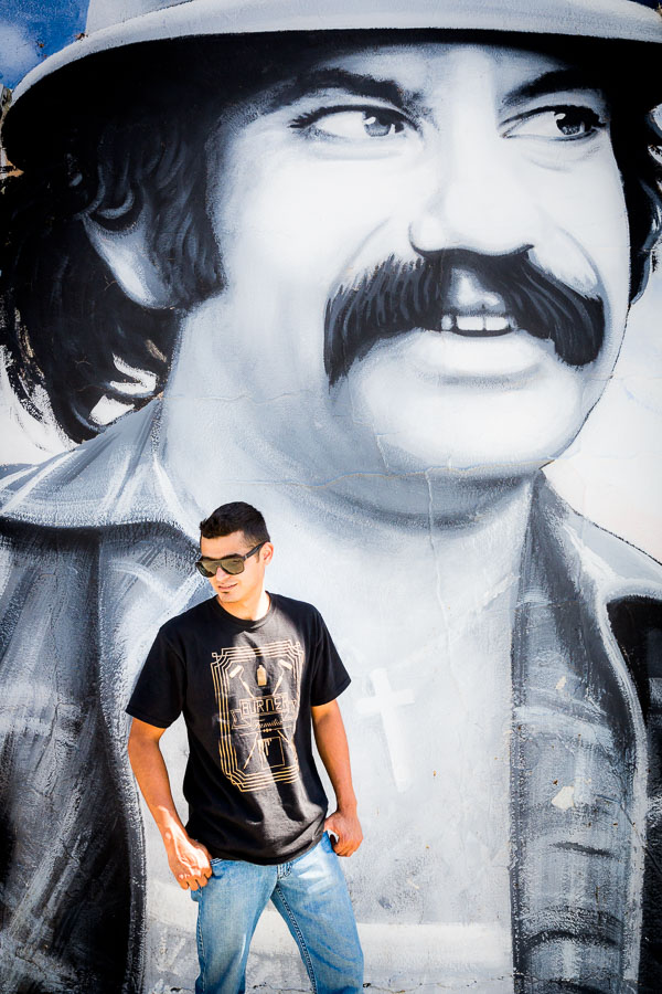 Artist Levi Ponce in Pacoima, Los Angeles, standing in front of a mural he painted of Cheech Marin. Photo by Jim Newberry.