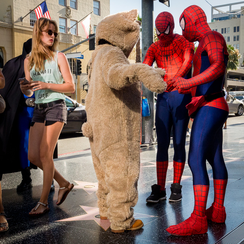 Two people in Spiderman costumes frisk someone in a bear costume, while onlooker walks by. On the Walk of Fame, Hollywood Boulevard, Los Angeles. Photo by Jim Newberry.